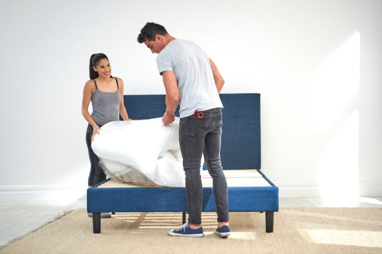 Couple unrolling a Haven mattress