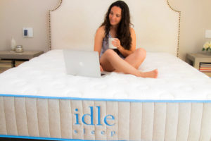 A woman sitting on an Idle Sleep mattress